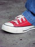 Zapato tenis y pantalones vaqueros rojos Foto de archivo libre de regalías