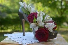 Zapato verde con el talón con las flores en la tabla Imagen de archivo