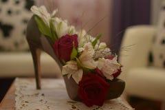Zapato verde con el talón con las flores en la tabla en sitio Foto de archivo