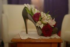 Zapato verde con el talón con las flores en la tabla en sitio Imagenes de archivo