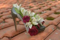 Zapato verde con el talón con las flores en el tejado Foto de archivo