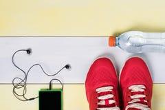 Zapato y teléfono rojos con los auriculares para los deportes, concepto en piso gris Fotografía de archivo