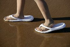Zapatos adultos para los pies de los niños en la arena de la playa Fotografía de archivo
