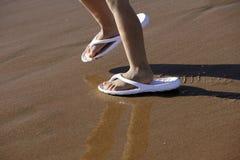Zapatos adultos para los pies de los niños en la arena de la playa Fotos de archivo libres de regalías