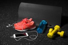 Zapatos anaranjados del deporte, pesas de gimnasia amarillas, estera de los pilates, botella azul, y teléfono con los auriculares Foto de archivo libre de regalías