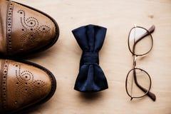 Zapatos, arco del lazo y vidrios en superficie de madera Fotografía de archivo libre de regalías