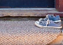 Zapatos azules gastados en el doormat Fotografía de archivo