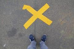 Zapatos azules que se colocan delante de una cruz Imagen de archivo libre de regalías