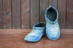Zapatos azules viejos alrededor de la pared de madera Foto de archivo libre de regalías