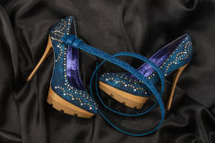 Zapatos azules y correa que mienten en el satén negro Foto de archivo