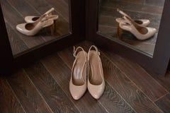 Zapatos beige de la novia en un piso de madera y reflexión dos en el espejo Fotografía de archivo