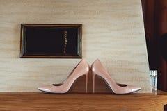 Zapatos beige hermosos de la boda con los tacones altos en un estante de madera, preparándose para la boda, detalles Fotos de archivo libres de regalías