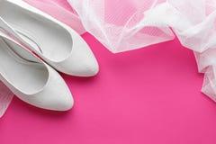 Zapatos blancos de la boda en fondo rosado Fotos de archivo