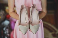 Zapatos blancos de la boda en las reuniones de la novia Fotografía de archivo