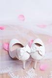 Zapatos blancos de la boda y pétalos color de rosa. Imagen de archivo libre de regalías