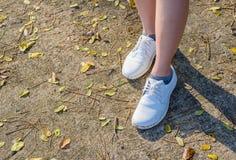 Zapatos blancos en la tierra imagenes de archivo