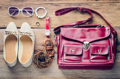 Zapatos, bolsos, accesorios para las mujeres, colocados en un piso de madera Foto de archivo