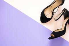 Zapatos clásicos elegantes de las sandalias del cuero del ` s de las mujeres negras con los tacones altos en fondo de papel multi Imagenes de archivo