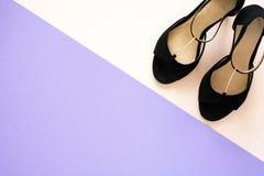Zapatos clásicos elegantes de las sandalias del cuero del ` s de las mujeres negras con los tacones altos en fondo de papel multi Imagen de archivo