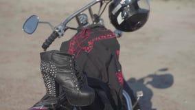Zapatos claveteados con los tacones altos y el vestido negro y rojo que mienten en el primer de la motocicleta La moto con el cas almacen de video