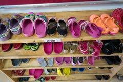 Zapatos coloridos de los niños en el estante en guardería Imágenes de archivo libres de regalías