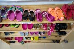 Zapatos coloridos de los niños en el estante en guardería Fotografía de archivo