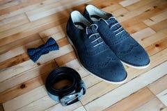 Zapatos, correa y bowtie de la boda en un fondo de madera Foto de archivo