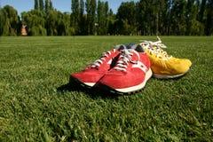 Zapatos corrientes rojos y amarillos en un campo de deportes Imagenes de archivo
