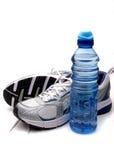 Zapatos corrientes y botella de agua Imagen de archivo