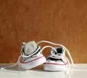 Zapatos de bebé con el fondo de la cartulina Foto de archivo