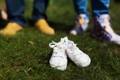Zapatos de bebé delante de los padres futuros Imagen de archivo