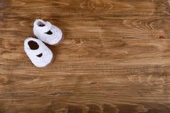 Zapatos de bebé hechos a mano hechos punto en el fondo de madera Fotos de archivo