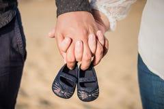 Zapatos de bebé de la explotación agrícola de la mujer embarazada foto de archivo
