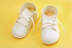 Zapatos de bebé sobre amarillo Fotos de archivo