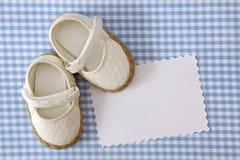 Zapatos de bebé y nota en blanco Fotografía de archivo