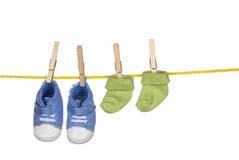 Zapatos de bebé y socka que cuelgan en una cuerda para tender la ropa Fotografía de archivo libre de regalías