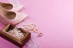 Zapatos de cuero beige con el tacón alto y los accesorios en fondo rosado Lugar para su texto Boda, compromiso ellos Fotografía de archivo