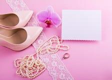 Zapatos de cuero beige con el tacón alto y los accesorios en fondo rosado Lugar para su texto Boda, compromiso ellos Foto de archivo libre de regalías