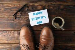 Zapatos de cuero de Brown, día de padres feliz de la inscripción, taza de café y vidrios en el fondo de madera, espacio para el t fotos de archivo