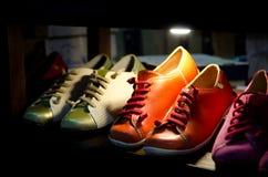 Zapatos de cuero coloridos en soporte Imagenes de archivo