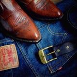 Zapatos de cuero, correa y vaqueros, desgaste clásico del vaquero Fotos de archivo libres de regalías