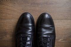 Zapatos de cuero de Brown en un piso de madera Imágenes de archivo libres de regalías