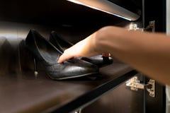 Zapatos de cuero de la señora negra en el estante de madera Foto de archivo