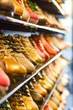 Zapatos de cuero del colourfull y del oro de la variedad en una tienda Imagenes de archivo