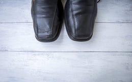 Zapatos de cuero del negro de los viejos hombres en el fondo de madera blanco de la textura Fotos de archivo