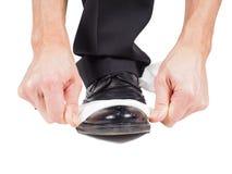 Zapatos de cuero negros brillantes de las manos masculinas Foto de archivo libre de regalías