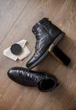 Zapatos de cuero negros en un piso de madera Imagenes de archivo