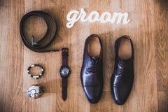 Zapatos de cuero negros hermosos y otros accesorios del novio en el fondo de madera Imagen de archivo libre de regalías
