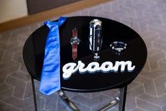 Zapatos de cuero negros hermosos y otros accesorios del novio en la tabla negra Foto de archivo libre de regalías