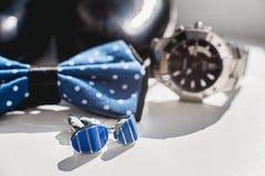 Zapatos de cuero negros, reloj, corbata de lazo azul y mancuernas, en un travesaño blanco de la ventana Accesorio para el vestido Fotografía de archivo